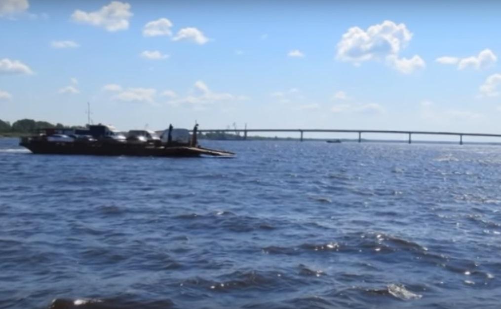 Новый мост стал неплохой декорацией для паромной переправы, остающейся единственным законным способом попасть на тот берег Камы. Фото: скриншот из видеоролика группы ИГГС Сарапул в социальных сетях.