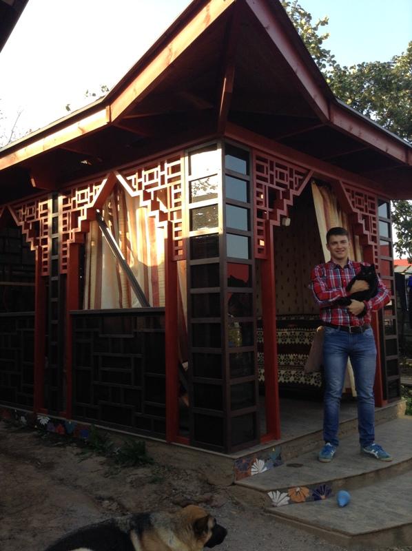 Максим Горшков позирует на фоне беседки, сделанной в китайском стиле. Фото из архива семьи