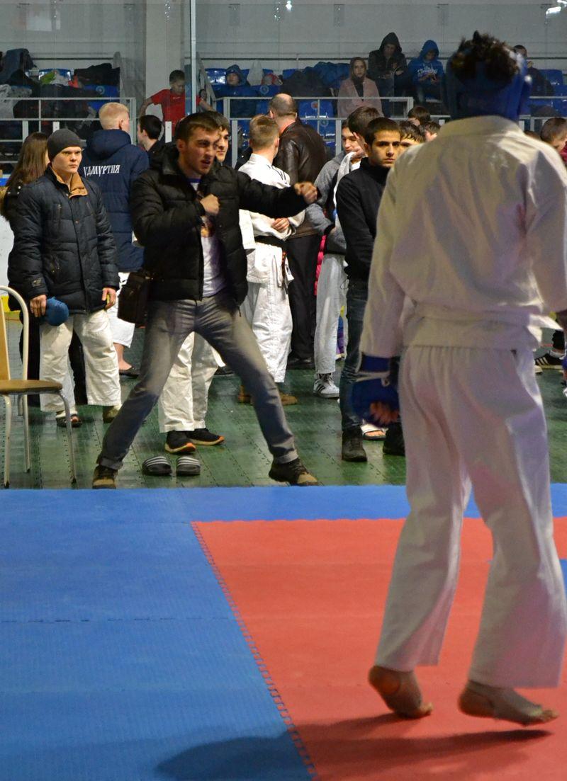 В паузе боя тренеры за ковром показывают ученикам, как им надо действовать на ковре. Фото: Александр Поскребышев