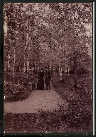 Новиков с женой Кларой и тремя детьми гуляют по саду.